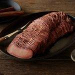 SADLER'S SMOKEHOUSE® TenderSplit beef brisket on a black serving platter.