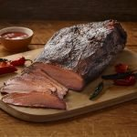 A side view of SADLER'S SMOKEHOUSE® whole brisket on a cutting board with some chilies and a ramekin or bbq sauce in the background.