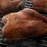 Three SADLER'S SMOKEHOUSE® whole turkeys smoking on a rack.