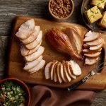 A carved SADLER'S SMOKEHOUSE® whole turkey on a cutting board with sides of corn bread, salad, and baked beans in the background.