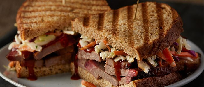 SADLER'S SMOKEHOUSE® brisket in a panini with bbq sauce and slaw.