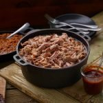 Cast iron pot of SADLER'S SMOKEHOUSE® pulled pork with a cast iron of baked beans behind it.