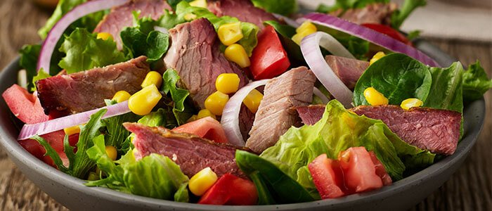 SADLER'S SMOKEHOUSE® brisket on a salad with red onion, corn, and tomato.