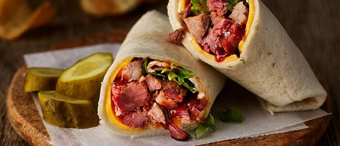 SADLER'S SMOKEHOUSE® brisket in a wrap with cheese, bbq sauce, and lettuce.