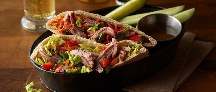 SADLER'S SMOKEHOUSE® pulled pork stuffed in pita pockets with salad.