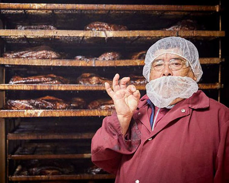 """Pit master standing in front of racks of bbq meat making the """"okay"""" symbol with his hand."""