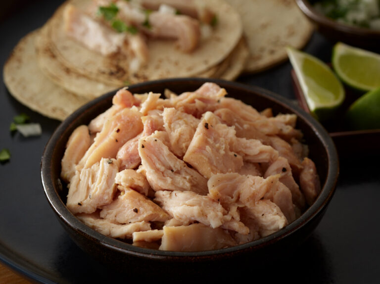 Bowl of Pulled Chicken with tortillas and limes around it.