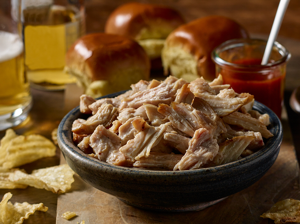 Bowl of pulled chicken with buns and potato chips around the bowl.